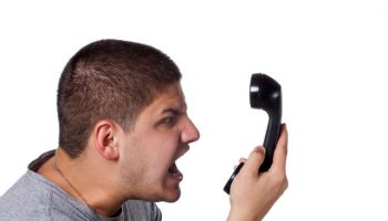 an-angry-and-irritated-young-man-screams-into-the-telephone-receiver-over-a-white-background_rYzWUoD0Ss